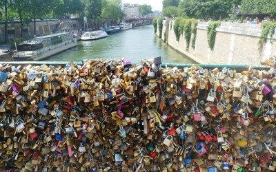 visit paris and france Padlocks fixed on a bridge over the Seine River in Paris, romantic places in paris